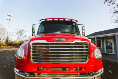 Freightliner red tow truck, front view.