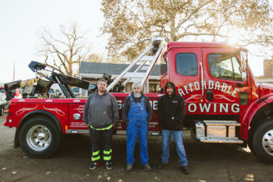 Owners and technician standing beside a heavy duty Affordable Towing truck